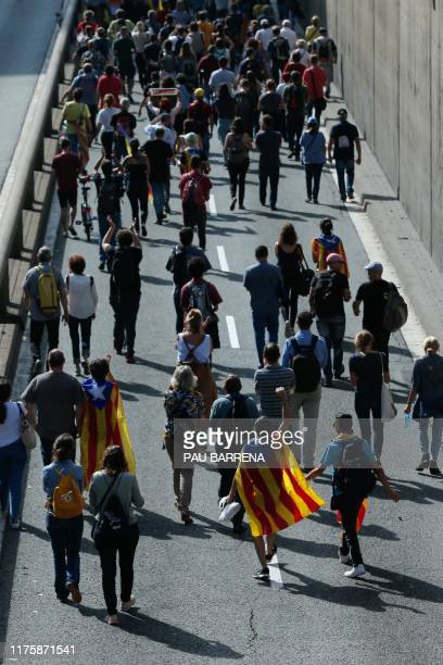 People walk in a street of Barcelona on October 14, 2019 as thousands of angry protesters took to the streets after Spain's Supreme Court sentenced...