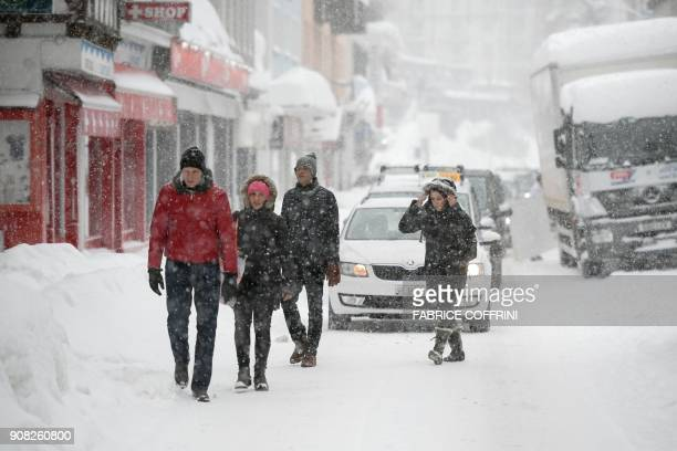 People walk in a street of Davos on January 21 as snow falls on the eve of the opening of the World Economic Forum 2018 annual meeting in Davos. The...