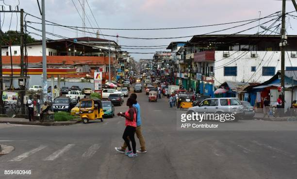 People walk in a street of Monrovia on October 9, 2017 on the eve of the Liberian presidential elections. Liberian President Ellen Johnson Sirleaf on...