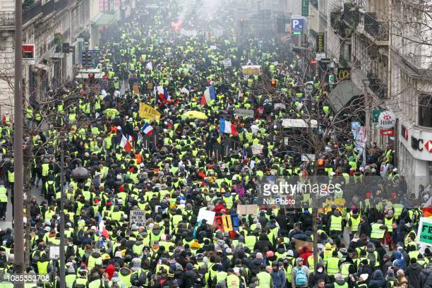 People walk in a street of Paris on January 19 2019 during a demonstration called by the yellow vests movement in a row of nationwide protest for the...