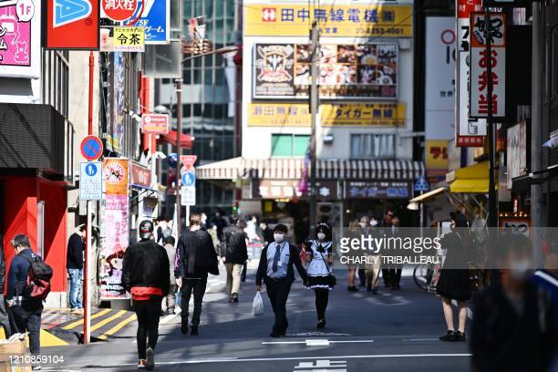 People walk in a street of the Tokyo's Akihabara area on April 24, 2020.