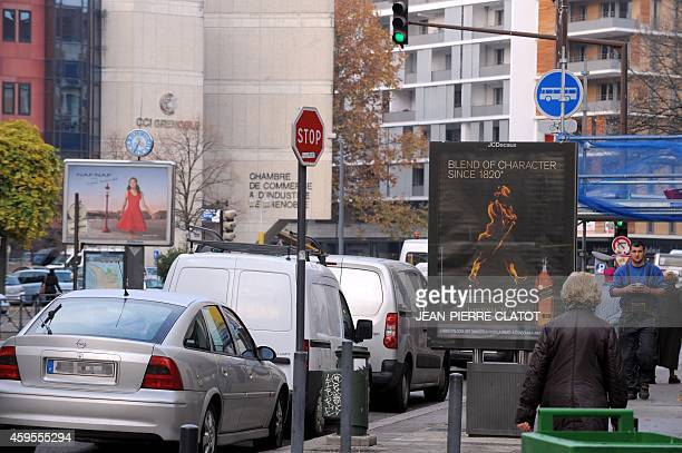 People walk in a street past advertising billboards, on November 25 in Grenoble a few days after the mayor of Grenoble announced the ban of...