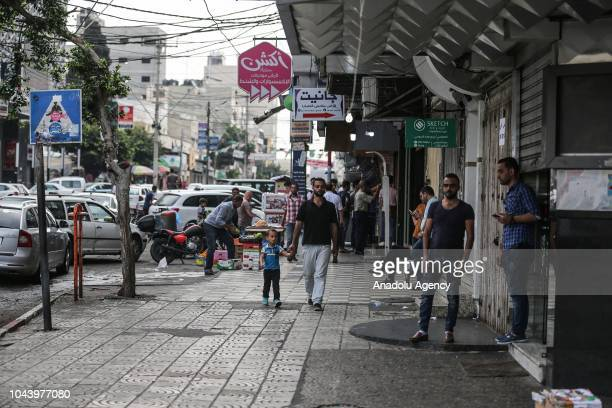 People walk in a street with closed shops in Gaza City Gaza on October 01 2018 during a general strike to protest against Israeli decision to...