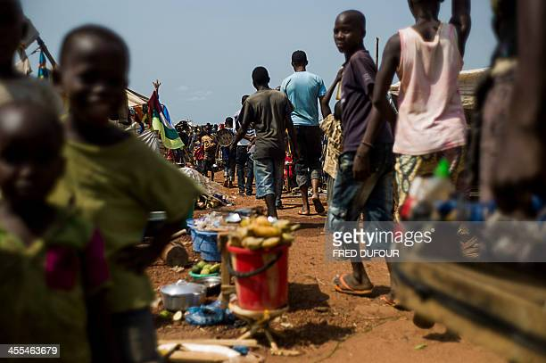 People walk in an internally displaced person camp near the airport of Bangui on December 12 2013 as aid officials fear that epidemics could spread...