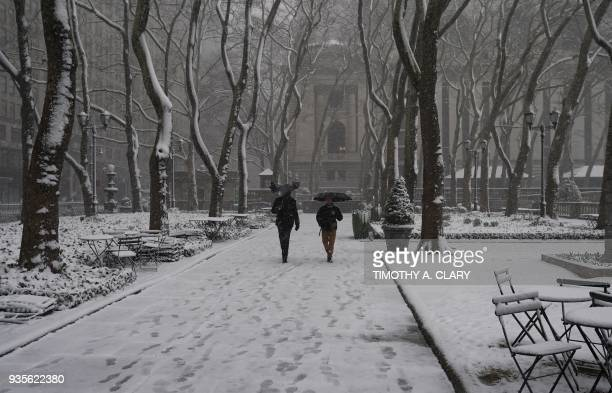 People walk in Bryant Park in New York on March 21 as the fourth nor'easter in a month hits the tristate area on the first full day of spring Winter...