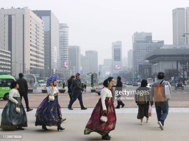 People walk in central Seoul amid haze on March 6 2019 South Korea proposed a joint project with China to use artificial rain to reduce air pollution...