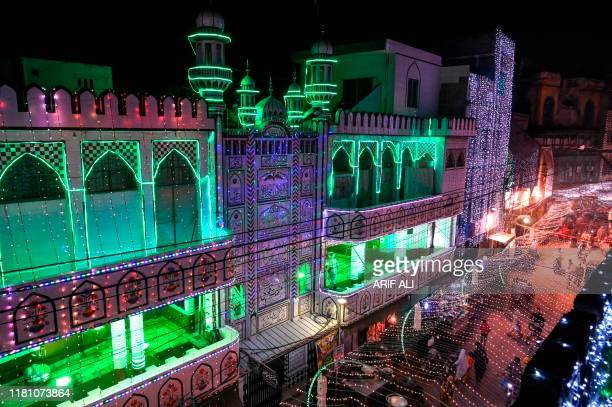 People walk in decorated street to mark the birthday celebration of the Prophet Mohammed, in Lahore on November 9, 2019. - The birthday of Prophet...