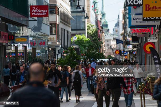 People walk in Drottninggatan during rush hour in Stockholm on May 29 amid the coronavirus COVID-19 pandemic. - Sweden's two biggest opposition...