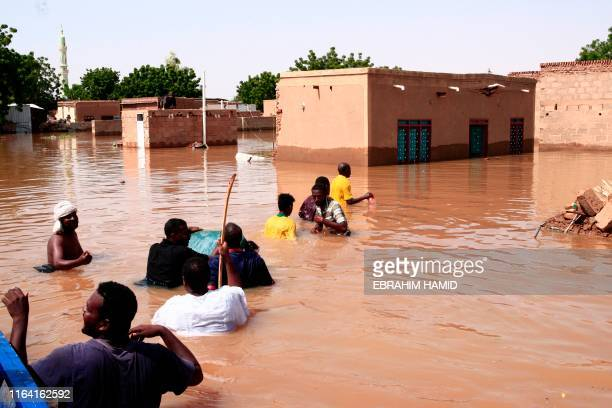 People walk in flood water in Wad Ramli village on the eastern banks of the Nile river, 50km north of Kharoum, on August 26, 2019. - Flash floods...