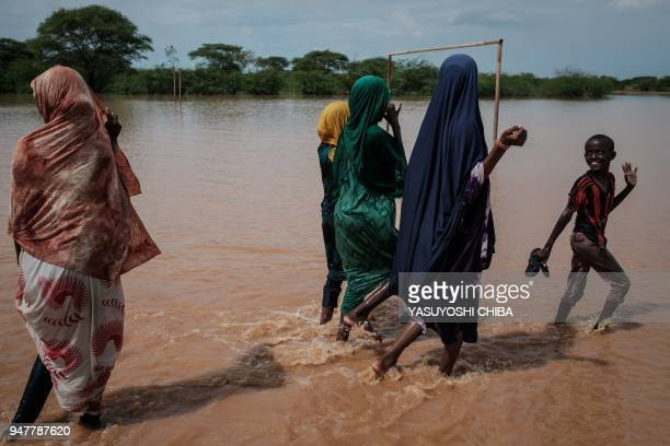 People walk in floodwaters after a heavy rainy season downpour at the Dadaab refugee complex, in the north-east of Kenya, on April 17, 2018. The...
