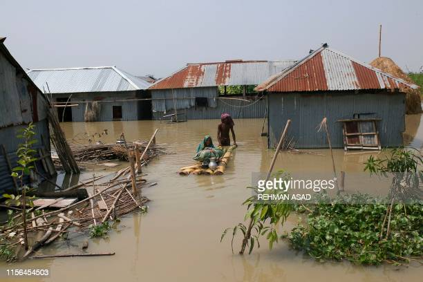 TOPSHOT People walk in floodwaters as they transport belongings on a makeshift raft following heavy monsoon rains at a flood affected area of...