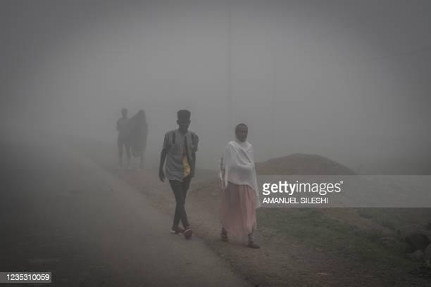People walk in fog in Amba Giorgis, 40 kilometers Northeast of the city of Gondar, Ethiopia, on September 17, 2021.