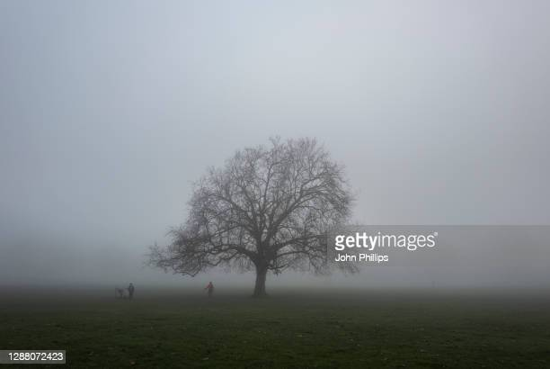 People walk in fog in Peckham Rye park on November 27, 2020 in London, England. The Met Office issued a yellow weather warning for the UK today for...