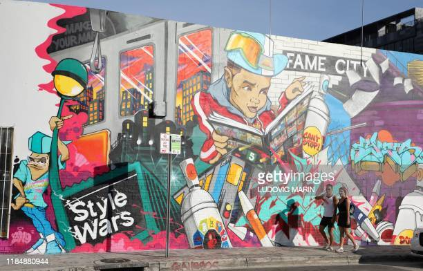 People walk in front a mural in Wynwood district street art in Miami on November 26 2019 / RESTRICTED TO EDITORIAL USE MANDATORY MENTION OF THE...