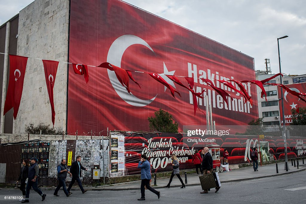 People walk in front of a billboard posted in Taksim square after the failed coup attempt displaying the words Hakimiyet Milletindir (Sovereignty belongs to the people/nation) on October 23, 2016 in Istanbul, Turkey. Since the failed coup attempt on July 15, 2016 which saw 240 people killed including 173 civilians, Turkish authorities initiated a state of emergency, leading to an unprecedented crackdown on individuals and organizations with links to US-based cleric Fethullah Gulen and his organization blamed for instigating the uprising. The purge, targeting teachers, journalists, soldiers, judges, academics, police, military leaders, schools and universities has so far seen approximately 100,000 people dismissed, 70,000 detained, 32,000 arrested, 130 media outlets closed and some 15 universities shuttered. The failed coup and subsequent purge only appears to have further bolstered the president's popularity and increased nationalism across the country with July 15th having been marked as a new national holiday. Turkish flags, already prominently displaying all over have increased in numbers, as well as posters of those killed fighting the coup plotters appearing in train stations and public squares. The Bosphorus Bridge in Istanbul, which saw heavy fighting during the coup has been renamed the '15th July Martyr's Bridge'. These changes, follow a year of instability in the country with constant terrorist attacks, an economic downturn, plummeting tourism, and a refugee crisis, all contributing to Turkish society undergoing its most dramatic restructuring in decades.