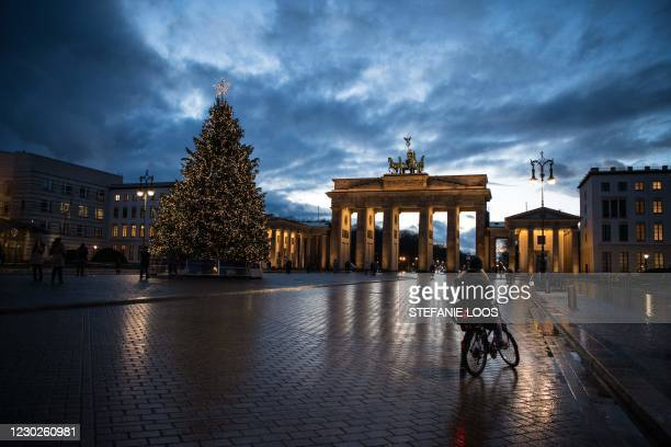 People walk in front of a Christmas tree at Brandenburger Gate during Germany's second lockdown amid the ongoing novel coronavirus / COVID-19...