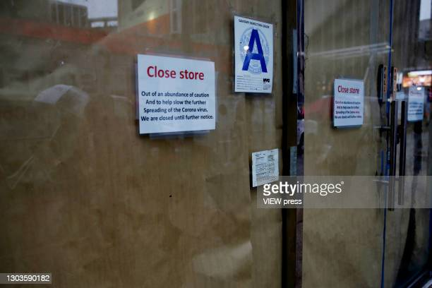 People walk in front of a closed store on February 22 in New York City. U.S. President Biden proposed changes to coronavirus aid program for small...