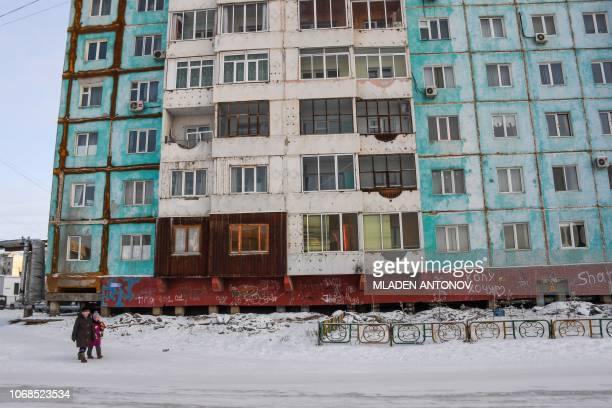 People walk in front of a cracked panel apartment building in the eastern Siberian city of Yakutsk on November 26 2018 Many houses in Yakutsk are...