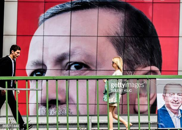 People walk in front of a giant poster of Turkish President Recet Tayyip Erdogan on April 6 2017 in Istanbul 10 days ahead of the referendum on...