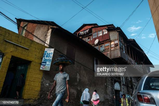People walk in front of a house designed by Armenian architect and urban engineer Minas Kherbekian who worked with Ethiopia's Emperor Menelik to...