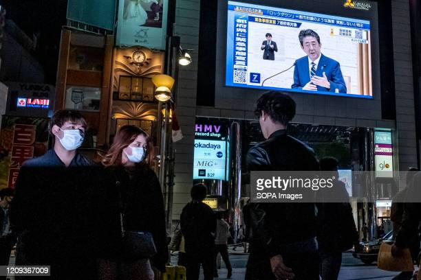 People walk in front of a large television screen as the Japanese Prime Minister Shinzo Abe speaks at a press conference and addressing the citizen...