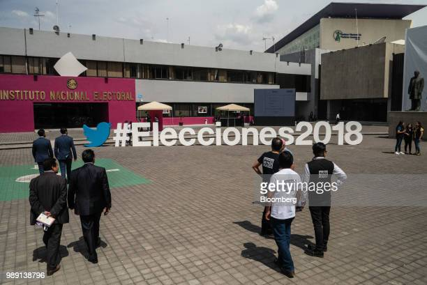 People walk in front of a large Twitter Inc hashtag sign at the National Electoral Institute headquarters in Mexico City Mexico on Sunday July 1 2018...