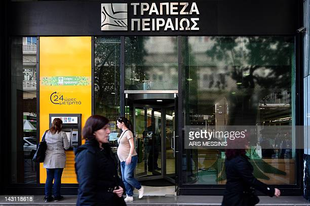 People walk in front of a Piraeus bank branch in Athens on April 19 2012 The four major Greek banks are preparing to announce massive losses Friday...
