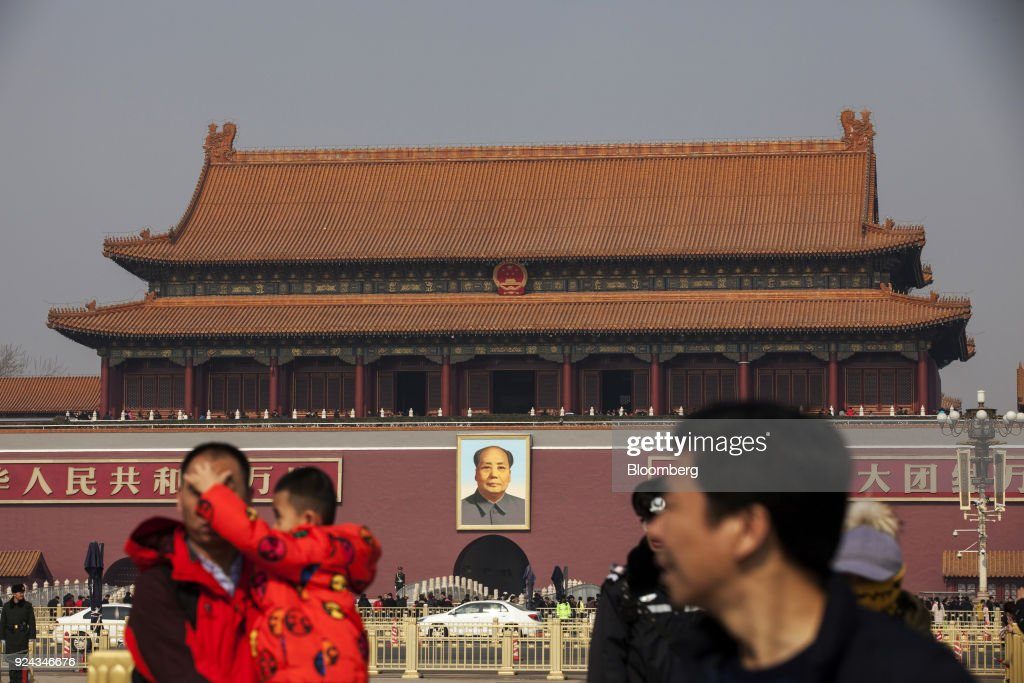 People walk in front of a portrait of former Chinese leader Mao Zedong at Tiananmen Square in Beijing, China, on Monday, Feb. 26, 2018. China's Communist Party is set to repeal presidential term limits in a move that would allowXi Jinpingto rule beyond 2023, completing the country's departure from a political system based on collective leadership. Photographer: Giulia Marchi/Bloomberg via Getty Images