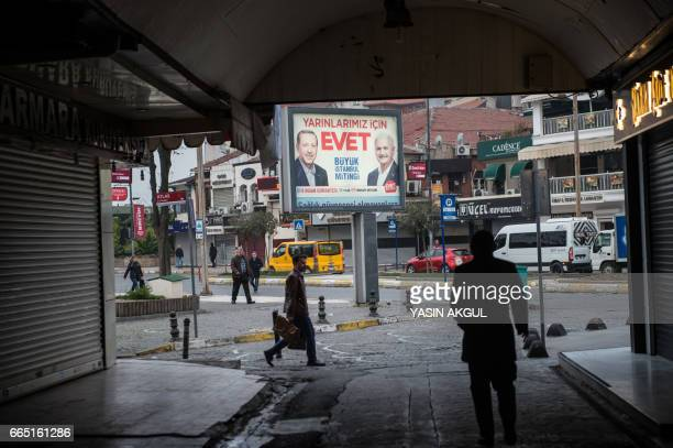 People walk in front of a poster of Turkish President Recep Tayyip Erdogan and Turkish Prime Minister Binali Yildirim on April 6 2017 in Istanbul 10...