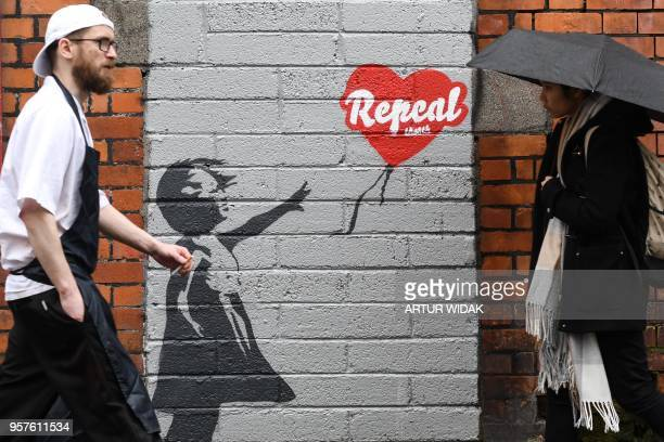 People walk in front of a prochoice mural based on a work by Banksy urging a yes vote in the referendum to repeal the eighth amendment of the Irish...