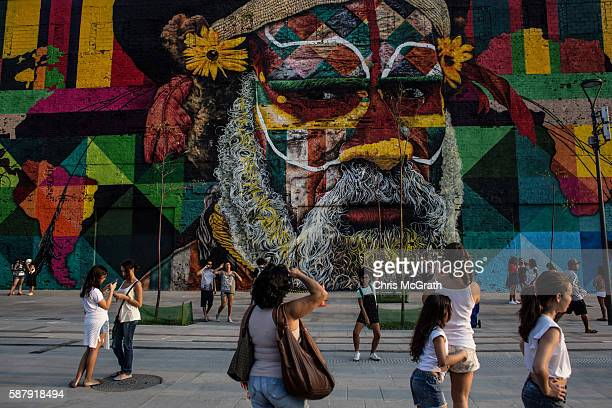 People walk in front of a section of a mural depicting an indigenous face created by Brazilian graffiti artist Eduardo Kobra along Olympic Boulevard...