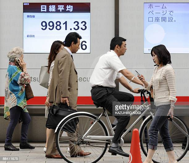 People walk in front of a share price board of the Tokyo Stock Exchange in downtown Tokyo on June 11 2009 Japanese share prices on June 11 briefly...