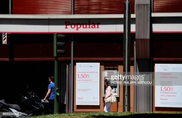 People walk in front of a Spanish Banco Popular's office in Madrid on June 7 2017 after European authorities announced the sale of Spain's Banco...