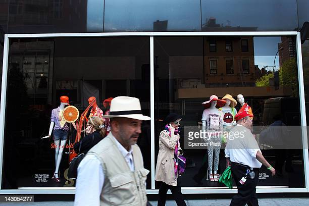 People walk in front of a window at the Bloomingdale's department store's flagship 59th Street store where a rally for a new contract is taking place...