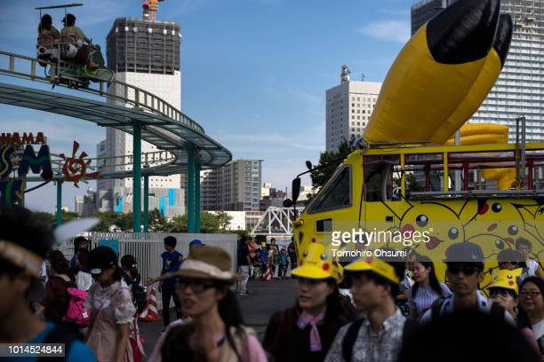 People walk in front of an amphibious bus featuring an advertisement of Pikachu a character from Pokemon series game titles during the Pikachu...