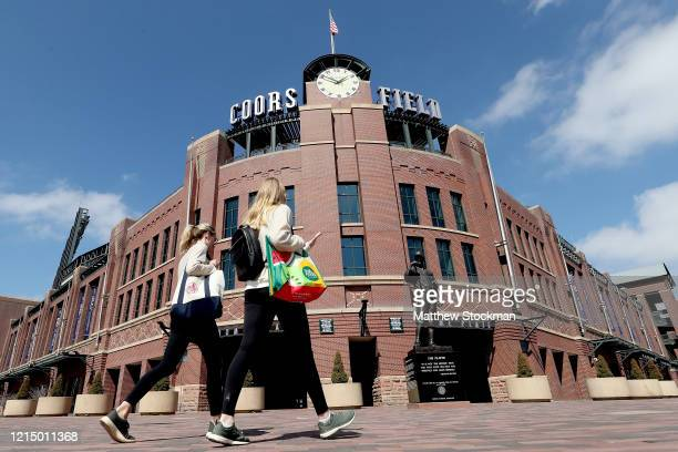 People walk in front of Coors Field on what was to be opening day for Major League Baseball on March 26, 2020 in Denver, Colorado. Major League...