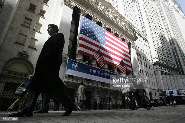 People walk in front of he New York Stock Exchange March 8, 2006 in New York City. The trading of NYSE Group shares, trading under the ticker symbol...