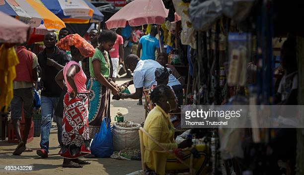 People walk in front of market stalls on a market on September 29 2015 in Beira Mozambique
