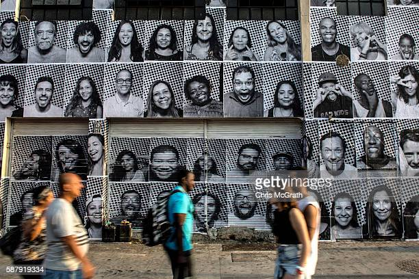 People walk in front of portraits produced by artist JR for his inside out project on August 8 2016 in Rio de Janeiro Brazil The artist JR has...