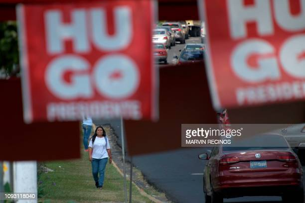 People walk in front of publicity of political parties on the eve of the first round of the national election, in San Salvador on February 2, 2019. -...