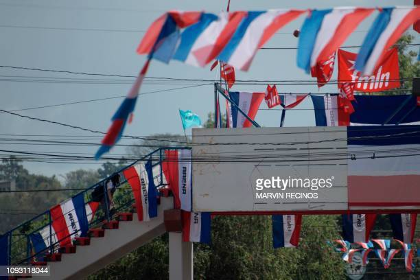 People walk in front of publicity of political parties on the eve of the first round of the national election in San Salvador on February 2 2019 More...