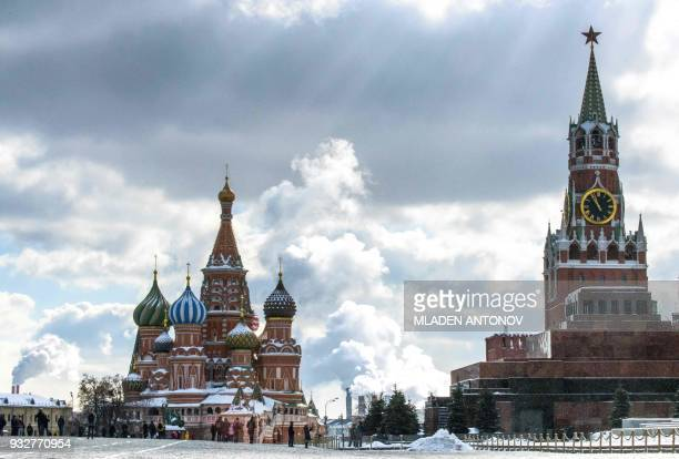 TOPSHOT People walk in front of St Basil's Cathedral and the Kremlin on Red Square in Moscow on March 16 2018 Russia will vote for President on March...