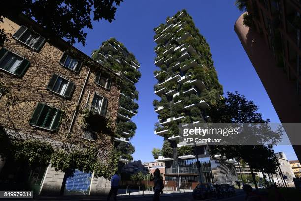 """People walk in front of the architectural complex designed by Studio Boeri, the """"Bosco Verticale"""" in the Porta Nuova area in Milan on September 5,..."""