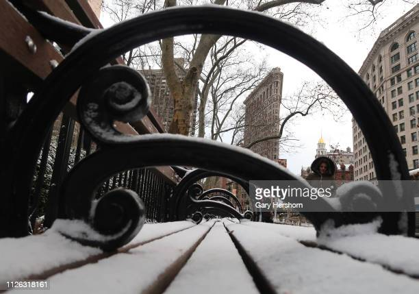 People walk in front of the Flatiron Building after a snow squall on January 30 2019 in New York City