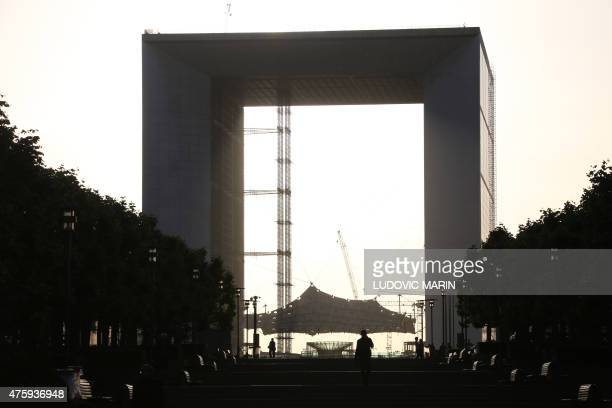 People walk in front of the Grande Arche of la Defense at sunset on June 3 2015 in Puteaux outside Paris AFP PHOTO / LUDOVIC MARIN