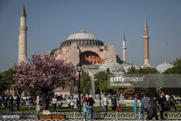 People Walk in front of the Hagia Sofia in Sultanahmet on April 24 2018 in Istanbul Turkey As peak tourism season approaches early booking figures...