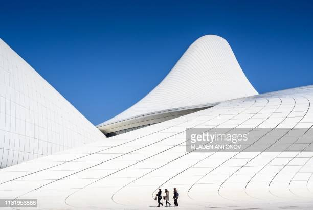 TOPSHOT People walk in front of the Heydar Aliyev Center in Baku on March 22 2019 The building was designed by IraqiBritish architect Zaha Hadid and...
