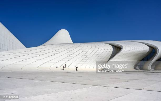 People walk in front of the Heydar Aliyev Center in Baku on March 22 2019 The building was designed by IraqiBritish architect Zaha Hadid and is...