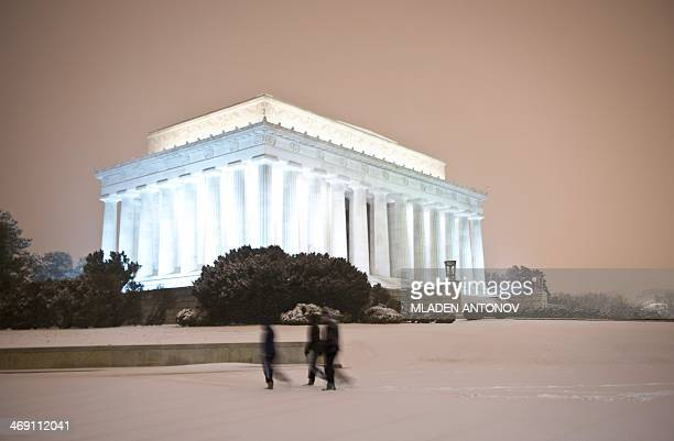 People walk in front of the Lincoln Memorial as a heavy snow storm hits Washington DC on February 13 2014 The eastern US in the grips of one of the...