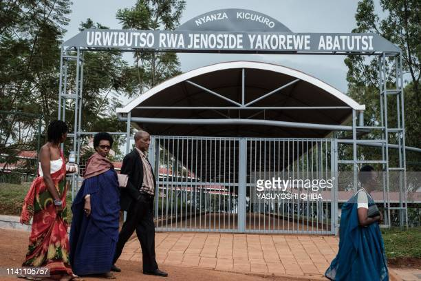 People walk in front of the main gate of the Nyanza Genocide Memorial in Kigali on May 4 2019 after the burial of 81 coffins containing newly...